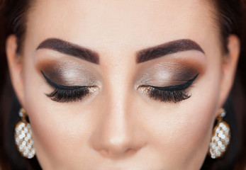 Beautiful Woman with long lashes and beautiful make-up in a beauty salon. Eyelash extension procedure.