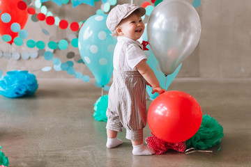 Reaching for balloons Baby boy sitting on floor reaching for balloons on his first birthday