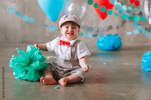 Happy Baby Boy Celebrating First Birthday Kids Party Decorated With Balloons And Colorful Banner