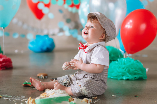 Messy baby boy eating cake on his 1st birthday looking up