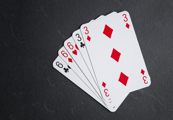Poker cards on a dark background. A system consisting of a triple and a pair.