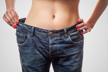 Closeup of slim waist of young woman standing in big jeans showing successful weight loss, indoor studio shot, isolated on light gray background, diet concept.