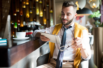 Portrait of  handsome bearded businessman sitting at bar counter using digital tablet  and smiling pensively, copy space