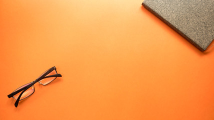 Wall Mural - glasses  with notebook on orange background