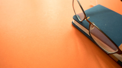 Wall Mural - glasses  with notebook on orange background.Close up