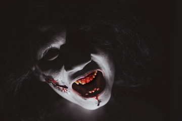 Closeup portrait of a creepy zombie woman with bloody wound on face