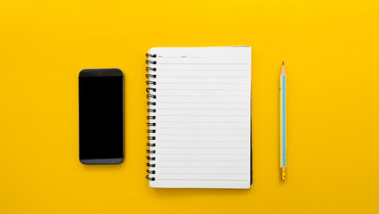 Wall Mural - Workplace with blank notebook and smartphone on yellow background.(Top-view )