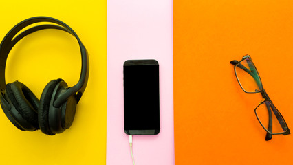 Wall Mural - Headphones,smartphone,glasses on a colorful background. Top View