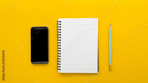 Wall mural Workplace with blank notebook and smartphone on yellow background.(Top-view )