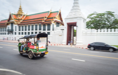 Bangkok / Thailand - 8-10-2017: green tuc tuc taxi driving tourists around in the city of Bangkok