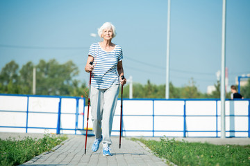 Full length portrait of active senior woman practicing Nordic walking with poles outdoors in park, copy space Wall mural