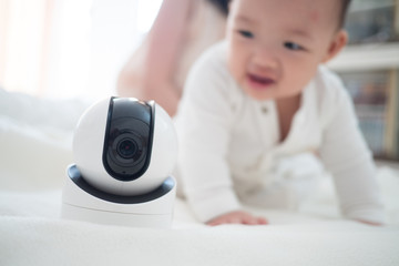 Baby monitor camera with blurred baby background for text space. concept of baby safty