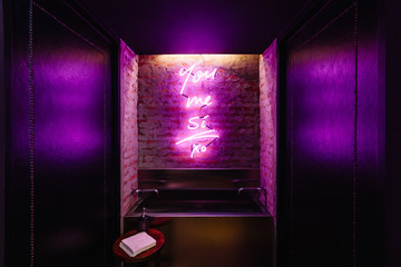 Sink with purple lighting words on the wall in front of toilet area at the restaurant in Bangkok, Thailand.
