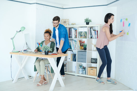 Full length portrait of group of modern designers working in small white office, focus on African-American woman sitting at desk, copy space