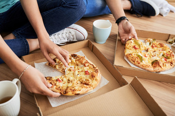 Young people sitting on room floor and eating delicious pizza