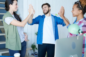 Portrait of three contemporary young people celebrating success and smiling cheerfully doing high five in modern office