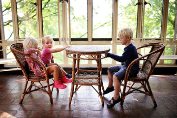 Three Little Children Sitting at an Old Bistro Table in a Sunroom Waiting for Food