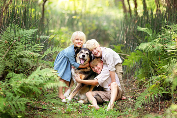 Three Happy Children Lovinglt Hugging the Pet Dog in the Forest