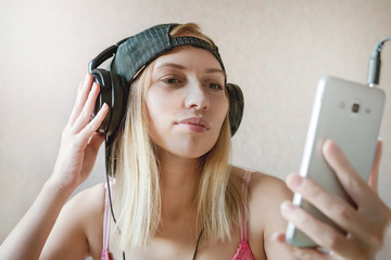 Cool girl listens music in headphones over white background. Online video chat. Communication. Taking pictures of themselves taking selfies. to watch a movie on a smartphone. audiobook.