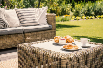 Beige color wicker table and settee on a porch during sunny afternoon in the garden. Croissants and...