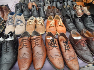 A large selection of second-hand men's leather shoes at the flea market