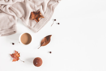 Autumn composition. Cup of coffee, women fashion sweater, autumn leaves on white background. Flat lay, top view, copy space