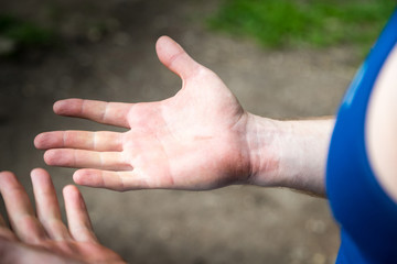 Male hands and the ground with grass in the background