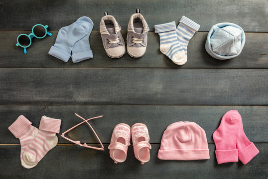 Baby boy and girl shoes and socks on blue wooden background