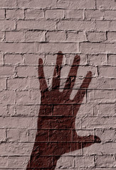 Shadow of a hand on a brick wall background
