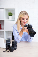 female photographer looking at display of digital camera in office