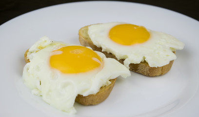 Two sandwiches with egg on a white plate.