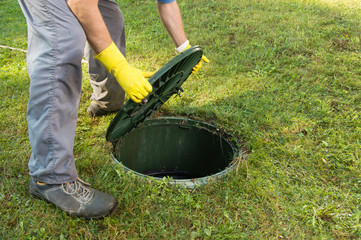 Opening septic tank lid. Cleaning and unblocking septic system and draining pipes.........