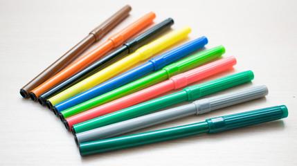 Set of multi-colored felt-tip pens on a light background.