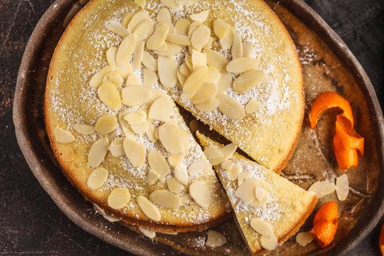 Almond cake on dark dish, top view, dark background.