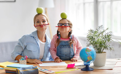 funny mother and child daughter doing homework writing and reading
