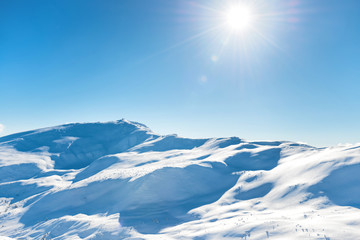 White winter mountains with snow and bright shining sun and sunrays