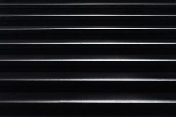 shiny horizontal metal strips on black, full frame view