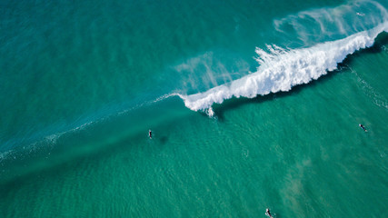 Surfers on beautiful day enyouing the waves in Australia, photographed from above using a drone.