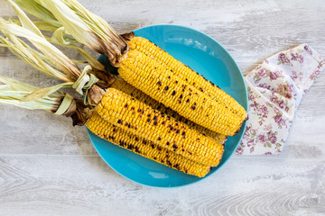 Corn baked in olive oil and salt on blue dish on light surface