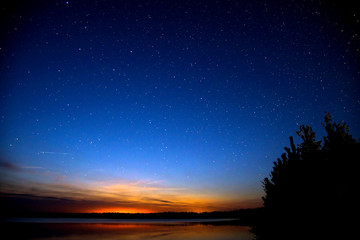 Amazing colorful sky after sunset by the river. Sunset and night sky with a lot of shiny stars.