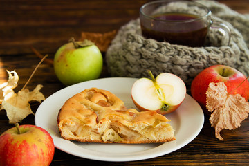 piec of an apple pie on a white plate on a wooden table