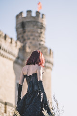 Pretty red haired medieval girl poses together castle.