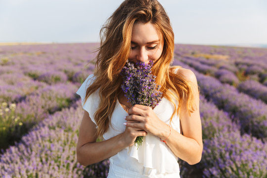 Photo of caucasian young woman in dress holding bouquet of flowers, while walking outdoor through lavender field in summer