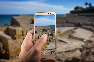Taking a picture with a smartphone in Roman amphitheatre in Tarragona, Costa Dorada, Catalonia, Spain