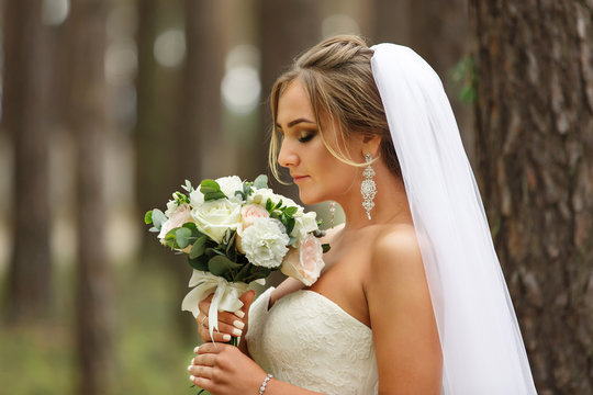 Beautiful bride with wedding bouquet. Portrait of bride with luxury wedding make-up and hairstyle. Marriage concept