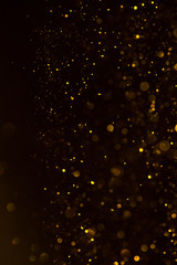 Glitter golden dust falling shiny abstract bokeh background