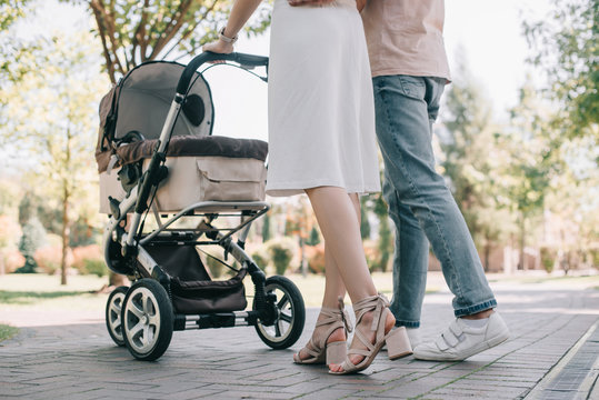 cropped image of parents walking with baby carriage in park