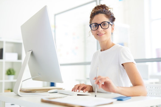 Young confident manager or designer sitting by her workplace in office in front of computer monitor