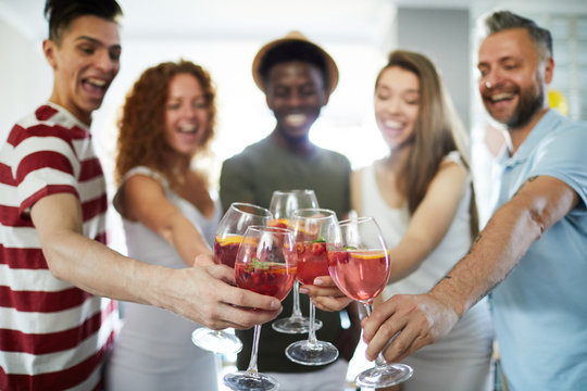 Happy humans clinking with homemade drinks in wineglasses during home gathering