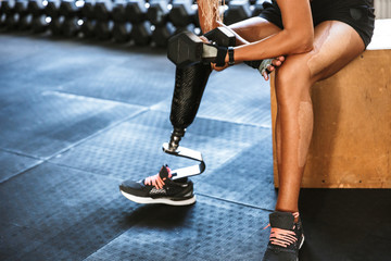 Cropped image of fitness disabled invalid woman wearing prosthesis in tracksuit, training and lifting dumbbell in gym